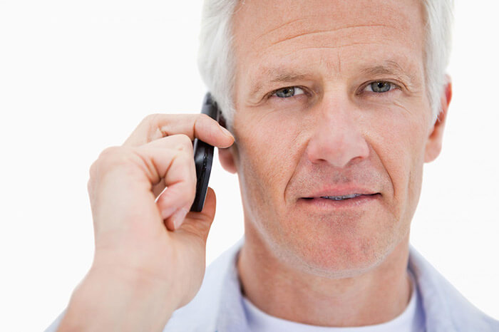 This is a picture of an old man having a phone call.